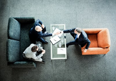 businessmen-shaking-hands-across-coffee-table-in-office-lobby-000024388516-double